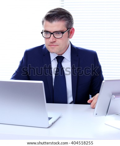 Portrait of a handsome business man wearing glasses working on his laptop in his office.