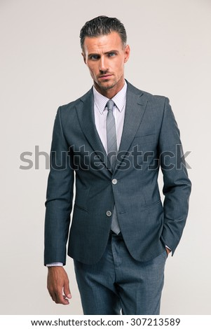 Portrait of a handsome businessman in suit standing isolated on a white background and looking at camera - stock photo