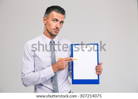 Portrait of a handsome businessman showing blank clipboard isolated on a white background - stock photo