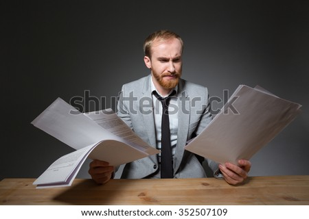 Portrait of a handsome businessman sitting at the table and reading papers over dark background - stock photo