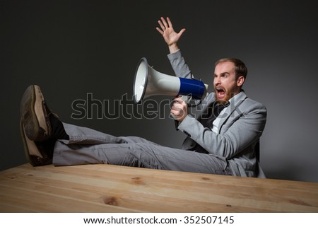 Portrait of a handsome businessman sitting at the table and shouting in megaphone over dark background - stock photo
