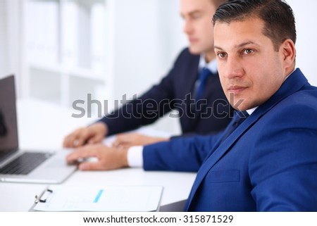 Portrait of a handsome businessman sitting in an office with colleagues in the background