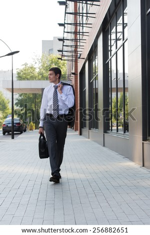 Portrait of a handsome businessman walking on the street near office building - stock photo