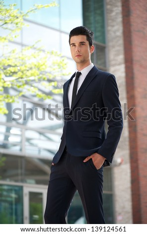 Portrait of a handsome businessman walking outdoors - stock photo