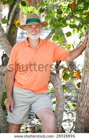 Portrait of a handsome, casually dressed senior man in a grove of trees. - stock photo