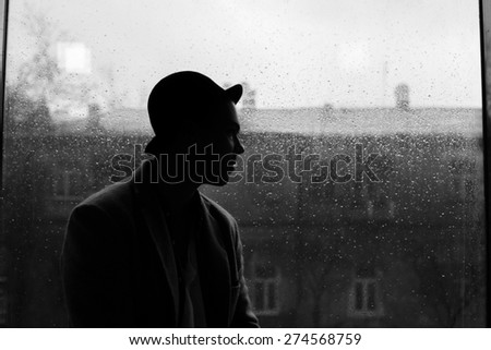 portrait of a handsome caucasian guy in hat silhouette on a rain drops on window and city view background - stock photo