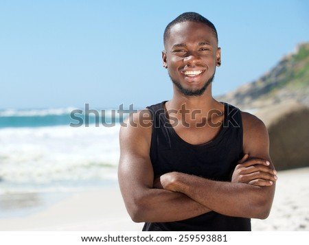 Portrait of a handsome cheerful man smiling at the beach - stock photo