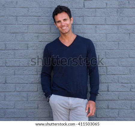 Portrait of a handsome confident man smiling against gray wall - stock photo