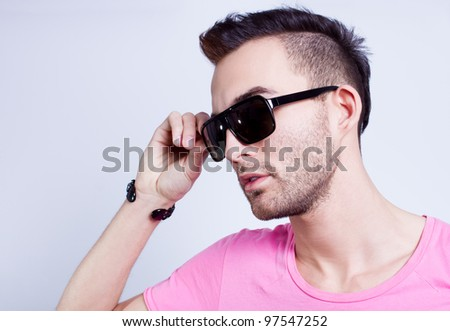portrait of a handsome fashion man wearing pink shirt on gray background - stock photo