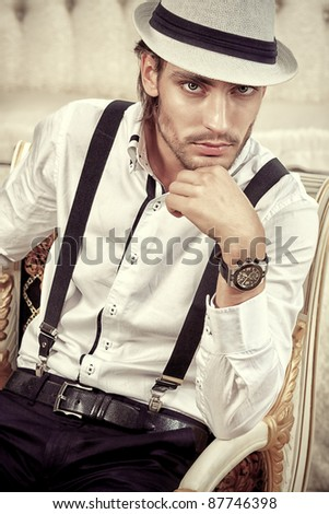 Portrait of a handsome fashionable man posing in the interior. - stock photo