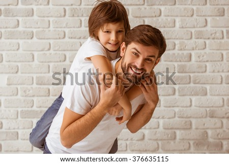 Portrait of a handsome father carrying his cute son on back. Both in white t-shirts smiling, standing against white brick wall. - stock photo
