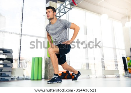 Portrait of a handsome fitness man doing warm-up exercises at gym - stock photo