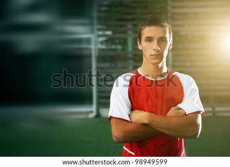 portrait of a handsome football player with his arms crossed in training - stock photo