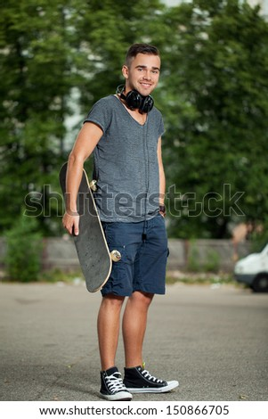 Portrait of a handsome guy who is wearing headphones and standing on his skateboard at a park - stock photo