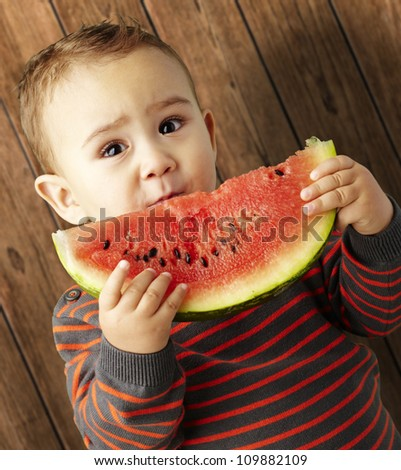 portrait of a handsome kid holding a watermelon against a wooden background