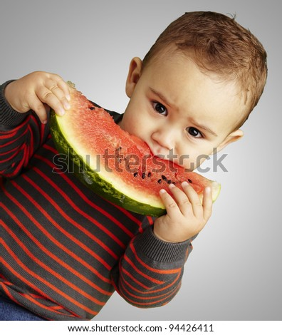 portrait of a handsome kid holding a watermelon and eating it over a grey background