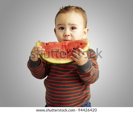 portrait of a handsome kid holding a watermelon over grey background