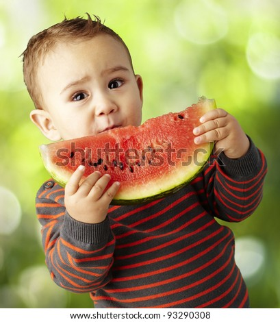portrait of a handsome kid holding a watermelon slice