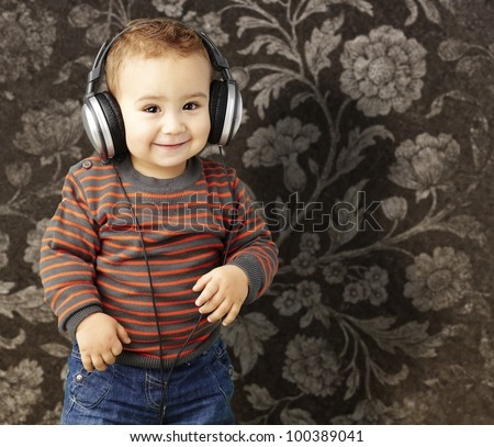 portrait of a handsome kid listening to music and smiling against a vintage background - stock photo