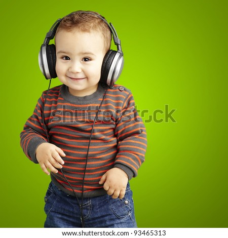 portrait of a handsome kid listening to music and smiling over green background - stock photo