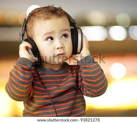 portrait of a handsome kid listening to music looking up against a city background - stock photo