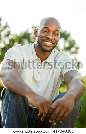 Portrait of a handsome late 20s black man sitting at a park in summer - stock photo