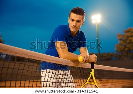 Portrait of a handsome male tennis player looking at camera outdoors - stock photo
