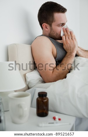 Portrait of a handsome man blowing his nose in his bedroom - stock photo