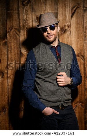Portrait of a handsome man by a wooden wall. Men's beauty, fashion. - stock photo