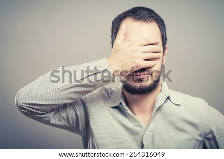 Portrait of a handsome man covering his eyes with hand  - stock photo
