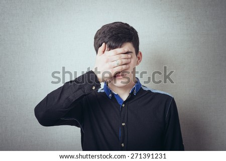 Portrait of a handsome man covering his eyes with hand in studio  - stock photo