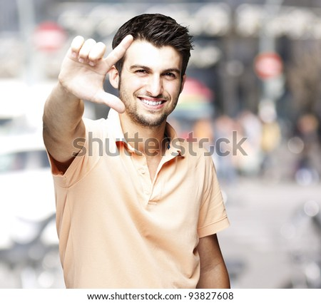 portrait of a handsome man doing a good symbol against a crowded city background - stock photo