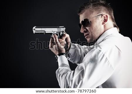 Portrait of a handsome man holding a gun. Studio shot. - stock photo