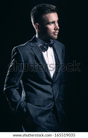 Portrait of a handsome man in a suit who is posing over a black background - stock photo