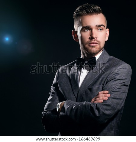 Portrait of a handsome man in a suit who is posing over a black background with a blue particles behind him - stock photo