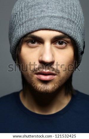 portrait of a handsome man in sports clothing and wearing a hat - stock photo