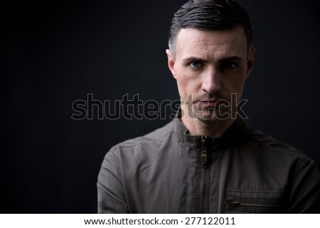 Portrait of a handsome man looking at camera over black background
