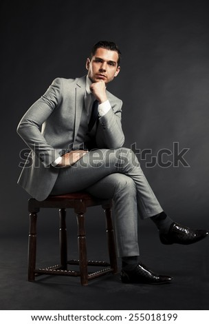 Portrait of a handsome man sitting in the armchair over black background. - stock photo
