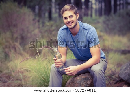 Portrait of a handsome man sitting on a stone in the nature