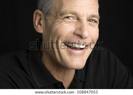 Portrait of a handsome man smiling directly to the camera - stock photo
