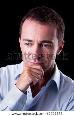 Portrait of a handsome  man thinking, on black background. Studio shot - stock photo