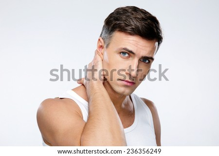 Portrait of a handsome man touching his neck over gray background - stock photo