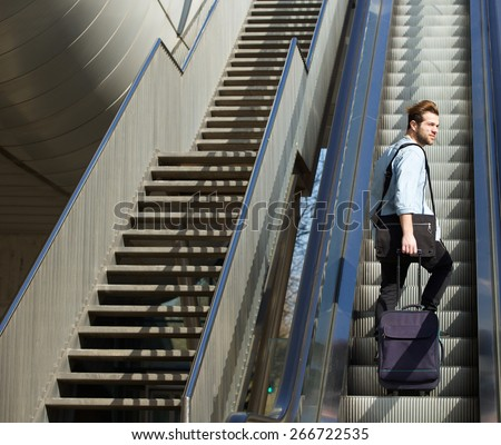 Portrait of a handsome man walking up escalator with travel bags - stock photo