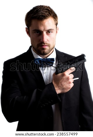 Portrait of a handsome man wearing bow tie and holding a gun - stock photo
