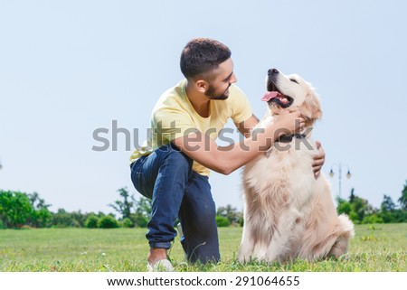 Portrait of a handsome man wearing yellow t-short and jeans with tattoo on his arm sitting on his hunkers, smiling and hugging his lovely golden retriever in the park - stock photo