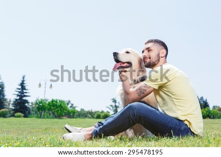 Portrait of a handsome man wearing yellow t-short and jeans with tattoo on his arm sitting on the grass, smiling and touching his lovely golden retriever smiling in the park - stock photo
