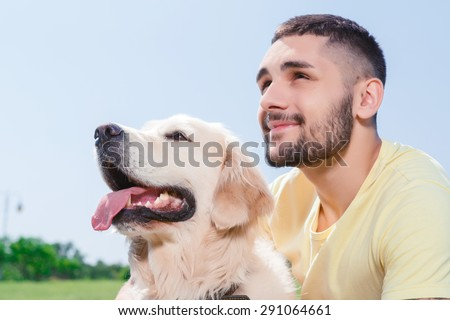 Portrait of a handsome man wearing yellow t-short sitting next to his lovely dog golden retriever smiling and looking in the sky - stock photo