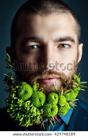 Portrait of a handsome man with a beard of green flowers. Men's beauty. Barbershop. - stock photo