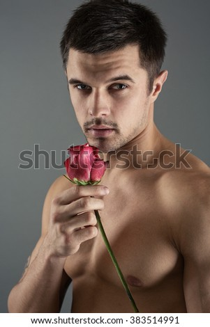 Portrait of a handsome man with a rose in his hand