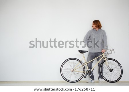 Portrait of a handsome man with bicycle in isolation - stock photo